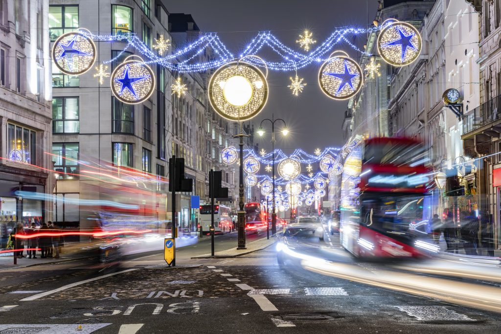 London shopping street during Christmas with festive lights and blurred road traffic