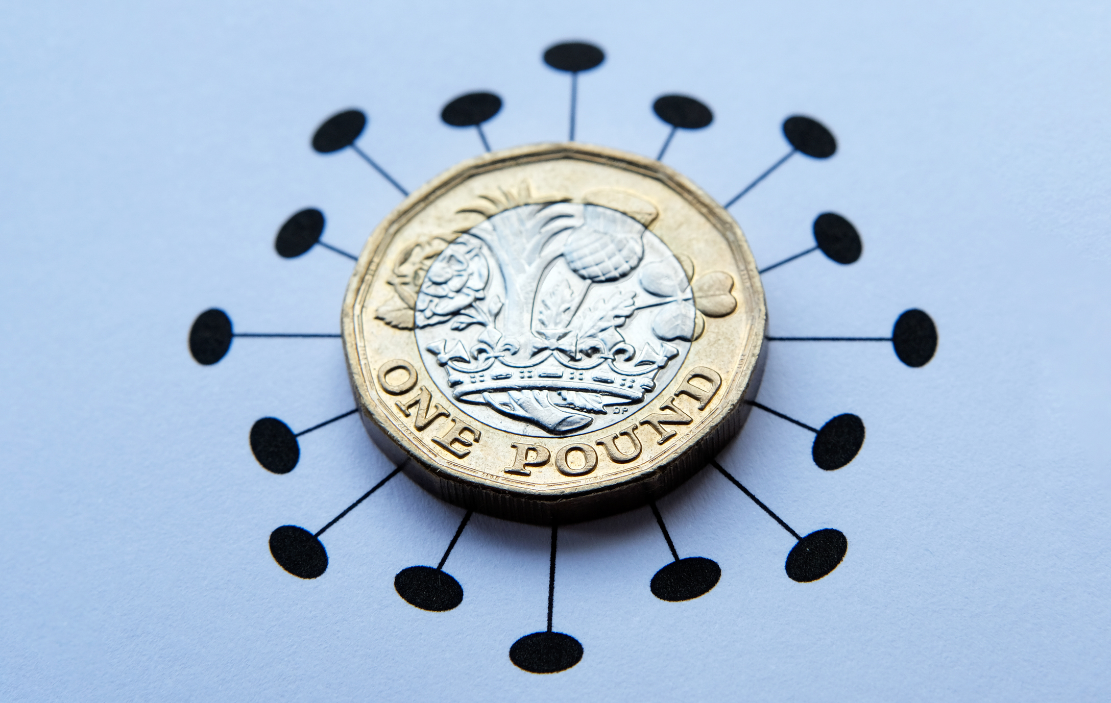 One pound coins placed on top of Coronavirus COVID-19 printed illustration.